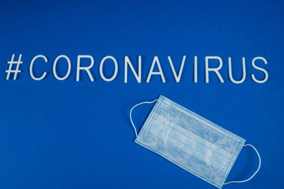 the word coronavirus laid with white letters on classic blue background. Respiratory protection mask next to the word coronavirus. News on social networks. Hashtag. Flat lay, copyspace.